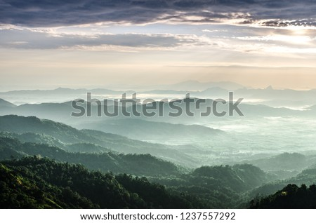 The sunrise shines down the green forest mountain in Myanmar. #1237557292