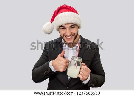 Cheerful young man holds glass of milk and look on camera. He shows big thumb up. Man wears Christmas hat and suit. Isolated on white background. #1237583530
