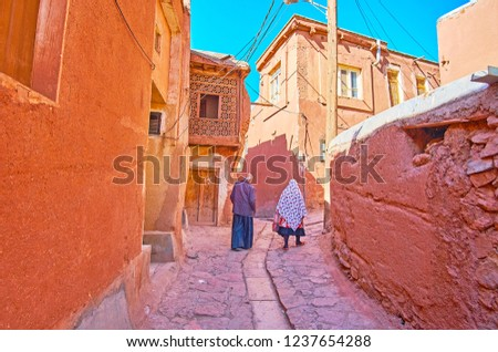 The senior couple in traditional Abyanaki clothes walks along the narrow ascent among the red adobe houses, Abyaneh, Iran. #1237654288
