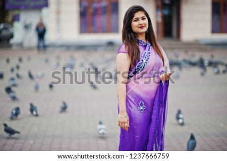Indian hindu girl at traditional violet saree posed at street against doves. #1237666759