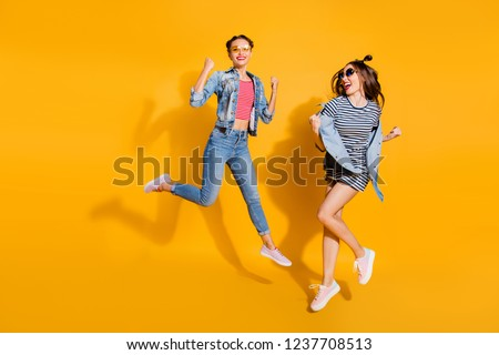 Full legs body size two dreamy charming lovely cute sweet lady in glasses spectacles cool trendy street style stylish casual denim jeans wear raised fists up isolated on yellow vivid background #1237708513