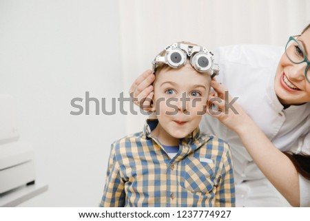 Child on reception doctor of ophthalmologist selects glasses of lens, check eye sight. #1237774927