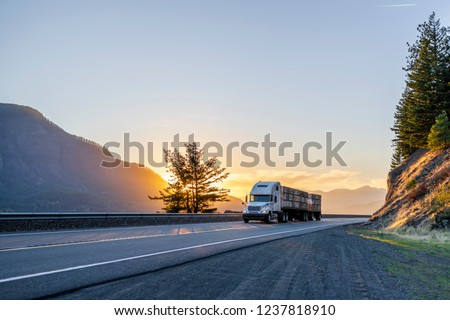 Big rig American white long haul powerful semi truck transporting boxes with fruits on flat bed semi trailer on straight evening road with scenic sunset in Columbia River Gorge #1237818910