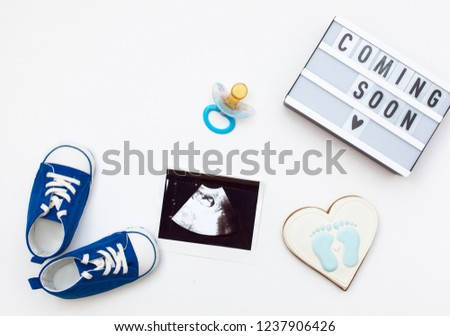 "flatlay pregnancy composition with space for text on white background. top view of children's accessories: toys, pacifier, baby screen, baby projector lamp ""coming soon"" and delicious gingerbread"