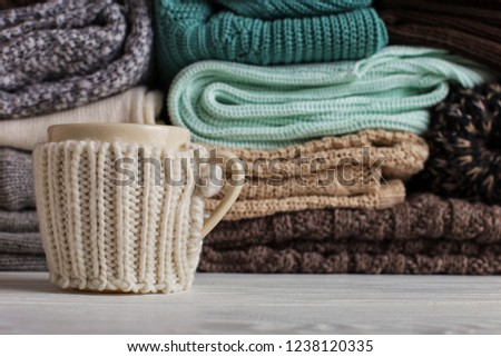 A stack of knitted clothes of different colors and textures, on the table next to a cup in a case. #1238120335