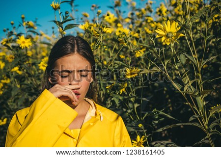 The girl suffers from pollen allergy during flowering and uses napkins. Young woman got nose allergy, flu sneezing nose. Woman is blowing her nose near flowers in bloom. Allergy #1238161405