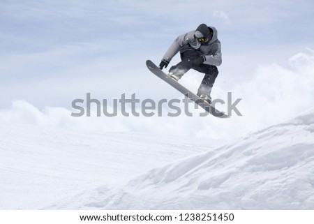 Snowboarder flying on the background of snowy slope. Extreme winter sports, snowboarding. #1238251450