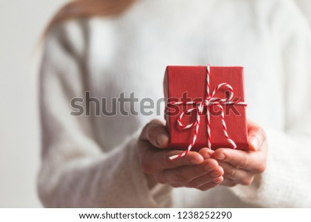Hands holding little gift with red bow. Close up.