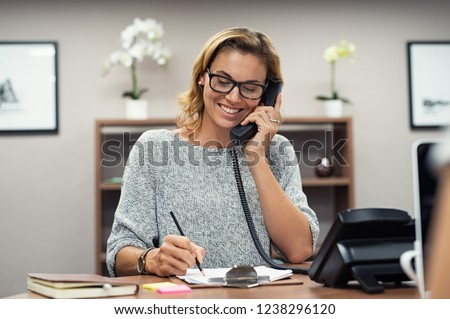 Beautiful mature woman talking on phone at creative office. Happy smiling businesswoman answering telephone at office desk. Casual business woman sitting at desk making telephone call and taking note. Royalty-Free Stock Photo #1238296120