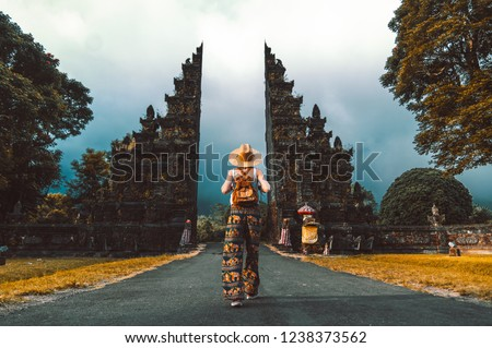 Tourist woman with backpack at vacation walking through the Hindu temple in Bali in Indonesia #1238373562
