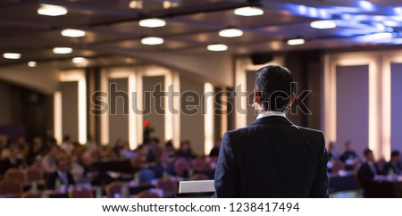 Presenter Presenting Presentation to Audience. Defocused Blurred Conference Meeting People. Lecturer on Stage. Speaker Giving Speech to Audience in Conference Hall Auditorium. Forum for Professionals  #1238417494