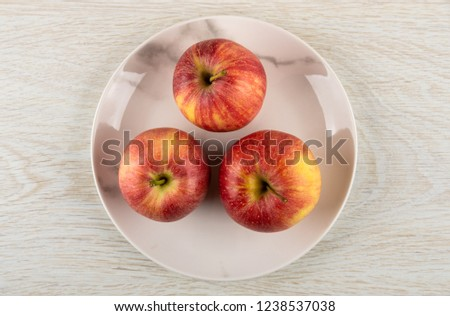Three red striped apples in glass plate on wooden table. Top view #1238537038