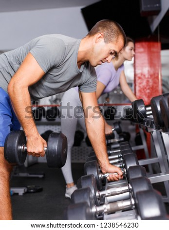 Cheerful man and girl choosing dumbbells on shelf at gym #1238546230