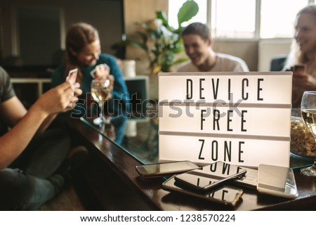 Mobile phones on table with device free zone sign. Group of young men and woman hanging out together at no phone zone. #1238570224