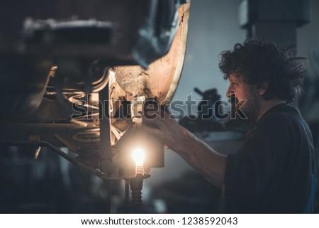 Mature mechanic at repair service station inspecting car suspension #1238592043