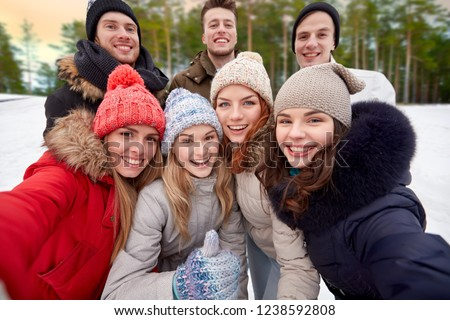 winter, friendship and people concept - group of friends taking selfie outdoors over natural background #1238592808