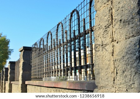 Concrete wall with a grooved brick block surface with a metal fence #1238656918