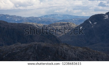 A mountain in the afternoon sun, surrounded by ridges under cloud shadows. Folgefonna national park, Norway. #1238683615