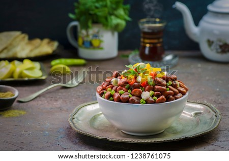 """Arabic cuisine; Egyptian traditional dish """"Ful medames"""".Middle Eastern delicious breakfast with cooked Fava beans topped with fresh ingredients. Served with cup of hot tea and fresh mint.  #1238761075"""