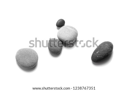 Scattered sea pebbles. Smooth gray and black stones isolated on white background. Top view #1238767351