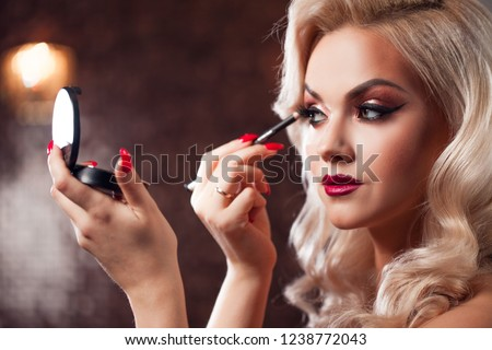 Beautiful young blonde makes a bright holiday makeup. Glamorous make-up. An attractive young woman paints the eyelashes #1238772043