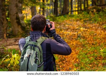 Back view male photographer in bright autumn forest #1238960503