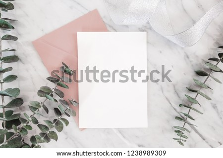 Wedding invitation mockup card with paper and envelope, roses, gifts, Eucalyptus, ribbon on marble background, top view, flat lay