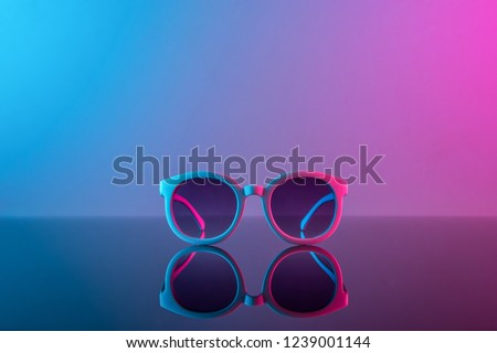 Stylish sunglasses shot using pink and blue abstract colored lighting with copy space. Royalty-Free Stock Photo #1239001144