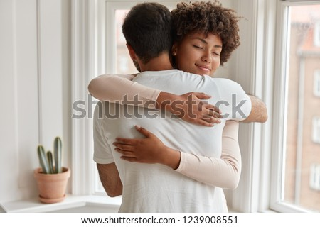Pleased dark skinned young woman gives warm hug to her boyfriend, being pleased, pose near window, have romantic relationship, stand in cozy room. Husband and wife feel pleased and togetherness #1239008551
