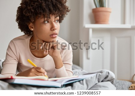Close up lifestyle image on thoughtful black girl with healthy skin, looks aside, holds chin, dressed in pyjamas, makes notes in diary, lies on bed, enjoyes bedtime and spare time. Woman copywriter #1239008557