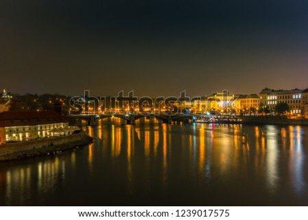Illuminated classical buildings and street lights reflecting on the Vltava river in Prague  in a cold winter night - 1 #1239017575