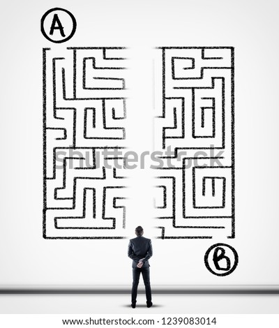 Thoughtful businessman solving a maze using a shortcut. Maze drawn on a white wall. Point a to point b. Royalty-Free Stock Photo #1239083014