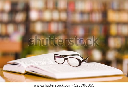 book and glasses on table in library #123908863