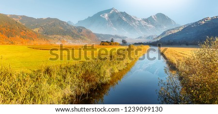 Wonderful picturesque Scene. Amazing Misty Morning. Beautiful nature Scenery. scenic view of Majestic Mountain Peak with river foreground, shoot in morning in Autumn season, Fantastic Alpine Landscape #1239099130