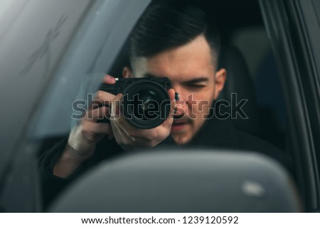 Young Male Spy Sits In The Car Taking Photos To The Camera With A Zoom Lens. Detective Agency Concept #1239120592