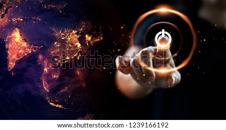 Finger pressing power button energy on earth at night background. Earth day. Environment and conservation. Energy saving concept. Royalty-Free Stock Photo #1239166192