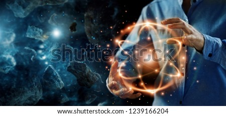 Abstract science, hands holding atomic particle, nuclear energy imagery and network connection on meteorites space planets background. #1239166204