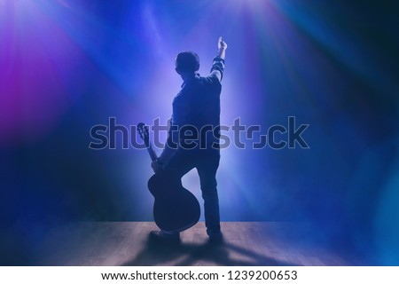 Musician with guitar on stage #1239200653