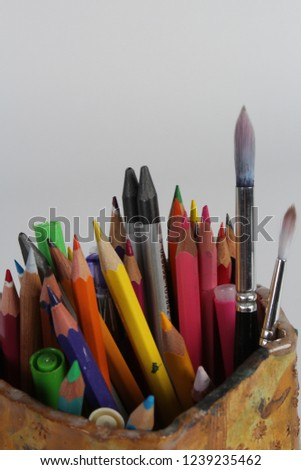 A collection of assorted pencils, crayons and brushes to form a group of art or craft tools for drawing and painting, colourful. UK #1239235462