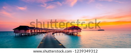 Amazing sunset panorama at Maldives. Luxury resort villas seascape with soft led lights under colorful sky. Beautiful twilight sky and colorful clouds. Beautiful beach background for vacation holiday #1239349312