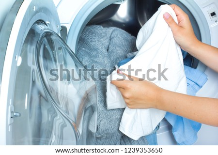 Preparing the wash cycle. Washing machine, hands and colourful clothes #1239353650