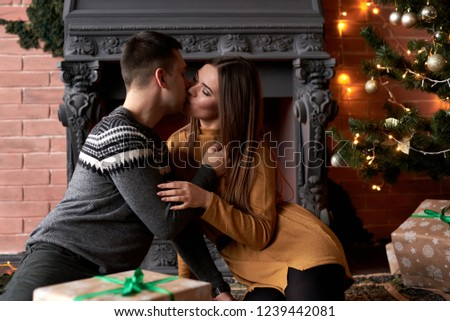 Young couple sitting in front of fireplace and Christmas tree kissing  #1239442081