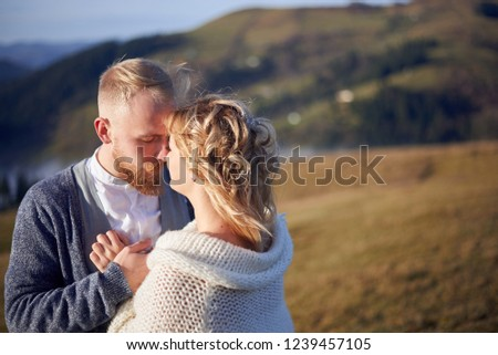 Young wedding couple in love, groom and bride, is standing, looking at each other, holding hands in the mountains  #1239457105