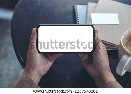 Top view mockup image of hands holding and using a black mobile phone with blank screen horizontally for watching with coffee cup and notebooks on table Royalty-Free Stock Photo #1239578281