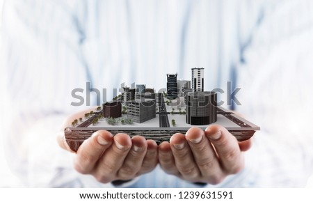 Close up of businessman holding modern office center model in hands. Mixed media #1239631591
