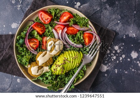 Vegan lentil meatballs salad with kale, avocado, tomato and tahini dressing on background, top view, copy space. #1239647551