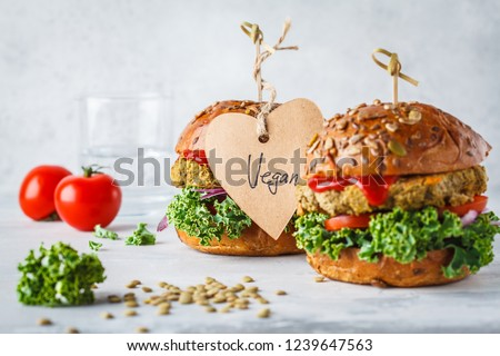 Vegan lentil burgers with kale and tomato sauce on a white background. Plant based food concept. Royalty-Free Stock Photo #1239647563