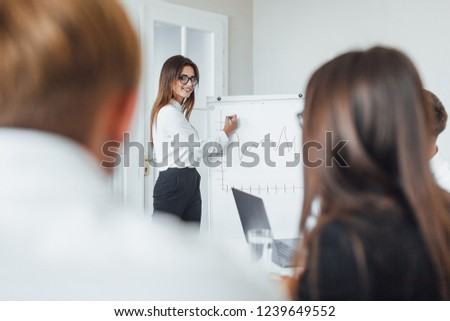 A young, modern business woman is presenting her colleagues, partners in the modern conference hall. #1239649552