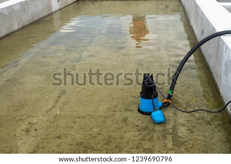 Submersible pump dewater construction site, pumping flood water sing deep well. #1239690796