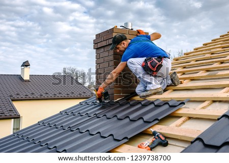 a professional master (roofer) with electric screwdriver covers repairs the roof #1239738700
